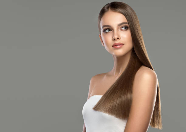 Young, brown haired beautiful model with long,  straight, well groomed hair. Hair care and hairdressing art. Young and pretty woman with soft smile on the face in demonstrating perfectly looking, dense and straight shiny hair. Natural gloss of healthy hair. Hair care and hairdressing art. straight hair stock pictures, royalty-free photos & images
