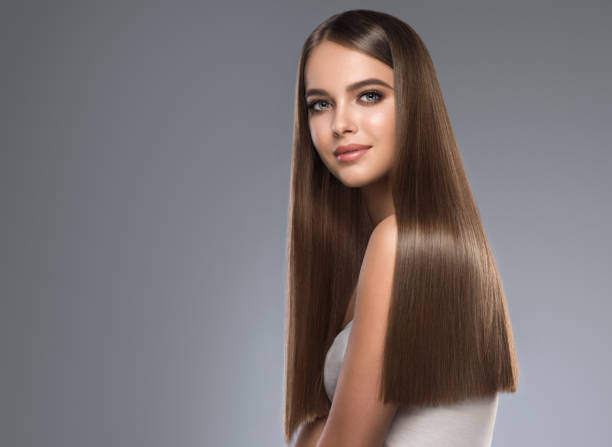 Young, brown haired beautiful model with long,  straight, well groomed hair. Hair care and hairdressing art. Young and pretty woman with soft smile on the face in demonstrating perfectly looking, dense and straight shiny hair. Natural gloss of healthy hair. Hair care and hairdressing art. straight stock pictures, royalty-free photos & images