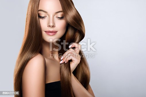 istock Young, brown haired beautiful model with long,  straight, well groomed hair is touching own hair with tenderness. 896422106