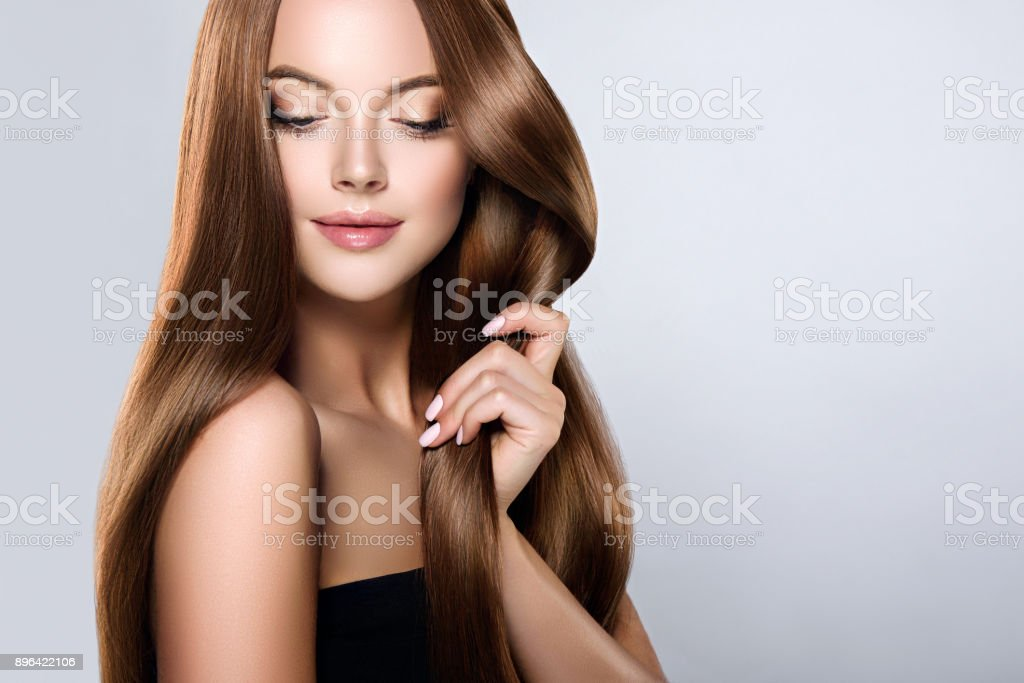 Young, brown haired beautiful model with long,  straight, well groomed hair is touching own hair with tenderness. stock photo
