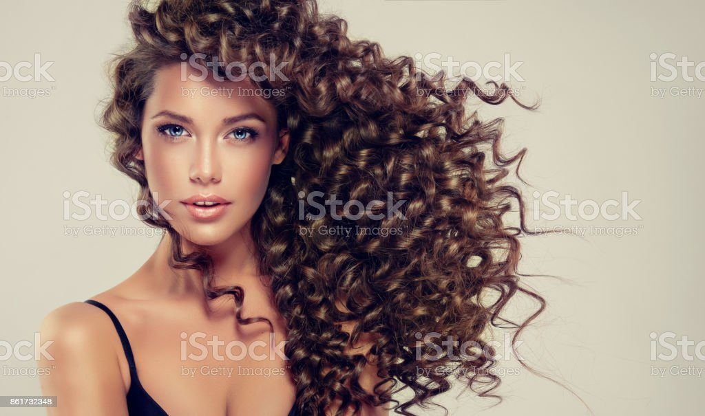 Young, brown haired beautiful model with long, wavy,well groomed hair.Tensed, spring-like curls on the hair. stock photo