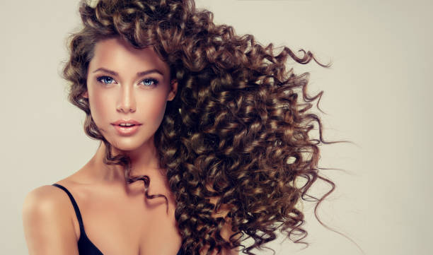 young, brown haired beautiful model with long, wavy,well groomed hair.tensed, spring-like curls on the hair. - hairstyle stock photos and pictures