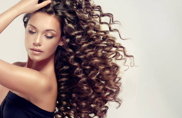 young, brown haired beautiful model with long, wavy,well groomed hair.tensed, spring-like curls on the hair. - thick stock pictures, royalty-free photos & images