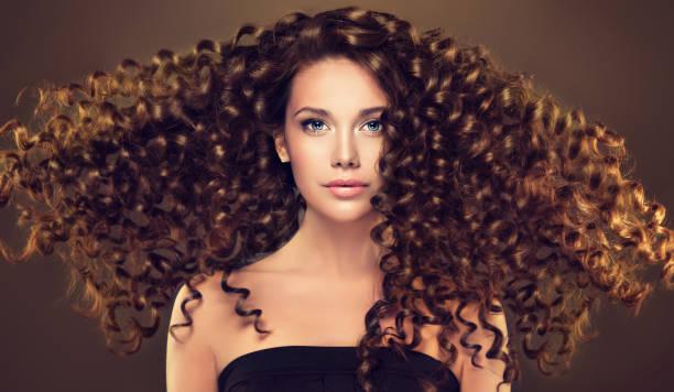 junge, braunen haaren schöne modell mit lang, wellig, gepflegtes haar. angespannt, frühlingshaften locken auf dem haar. - krause haare stock-fotos und bilder