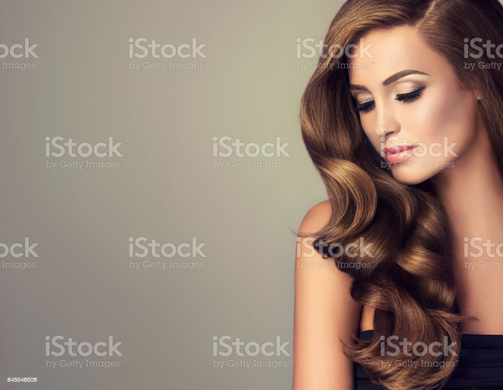 Young, brown haired woman with voluminous hair. Beautiful model with...
