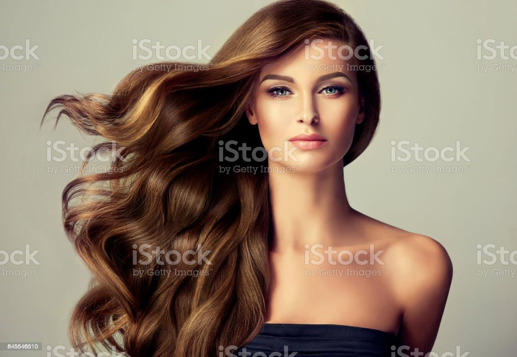 Young, brown haired beautiful model with long, wavy,well groomed hair. Flying hair. stock photo