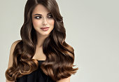 Young, brown haired woman  with curly and voluminous hair. Beautiful model with long, dense wavy hairstyle and vivid make-up. Perfect hair waves .Incredibly undulating and shiny hair.