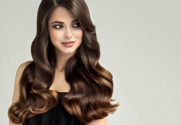 genç, kahverengi saçlı güzel modeli ile uzun, kıvırcık, bakımlı saç. mükemmel saç dalgalar. - tüy vücut parçaları stok fotoğraflar ve resimler