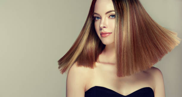 Young, brown haired beautiful model with middle length, straight, well groomed hair. Hair care and hairdressing art. Young and pretty woman with soft smile on the face in demonstrating perfectly looking, middle length straight, shiny hair. Trendy hairstyle. Hair care and hairdressing art. straight hair stock pictures, royalty-free photos & images