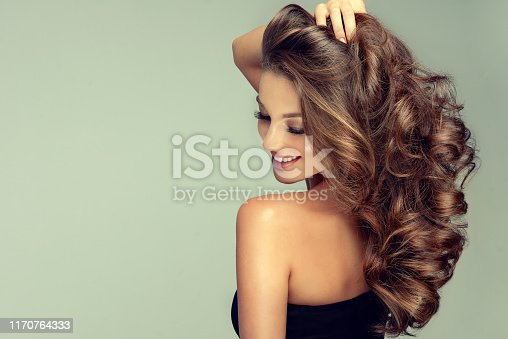 Young, tenderly smiling brown haired woman with perfect and voluminous curls, is touching softly owne hair.Beautiful model is showing long, dense, curly hairstyle and vivid makeup. Hair care ,hairdressing and styling.