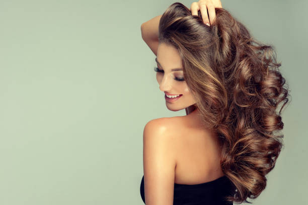 Young, brown haired woman is touching softly owne hair. Hair care. Young, tenderly smiling brown haired woman with perfect and voluminous curls, is touching softly owne hair.Beautiful model is showing long, dense, curly hairstyle and vivid makeup. Hair care ,hairdressing and styling. curly hair stock pictures, royalty-free photos & images