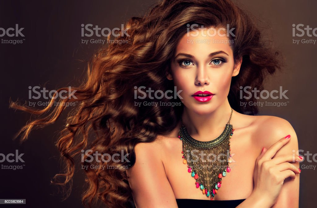 Young, brown haired woman with dense, shiny and wavy hair. Beautiful...