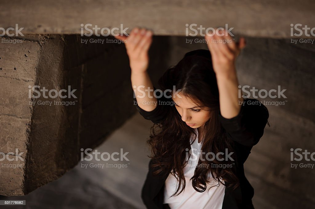 Young brunet woman  outside in black jacket hands in front . stock photo