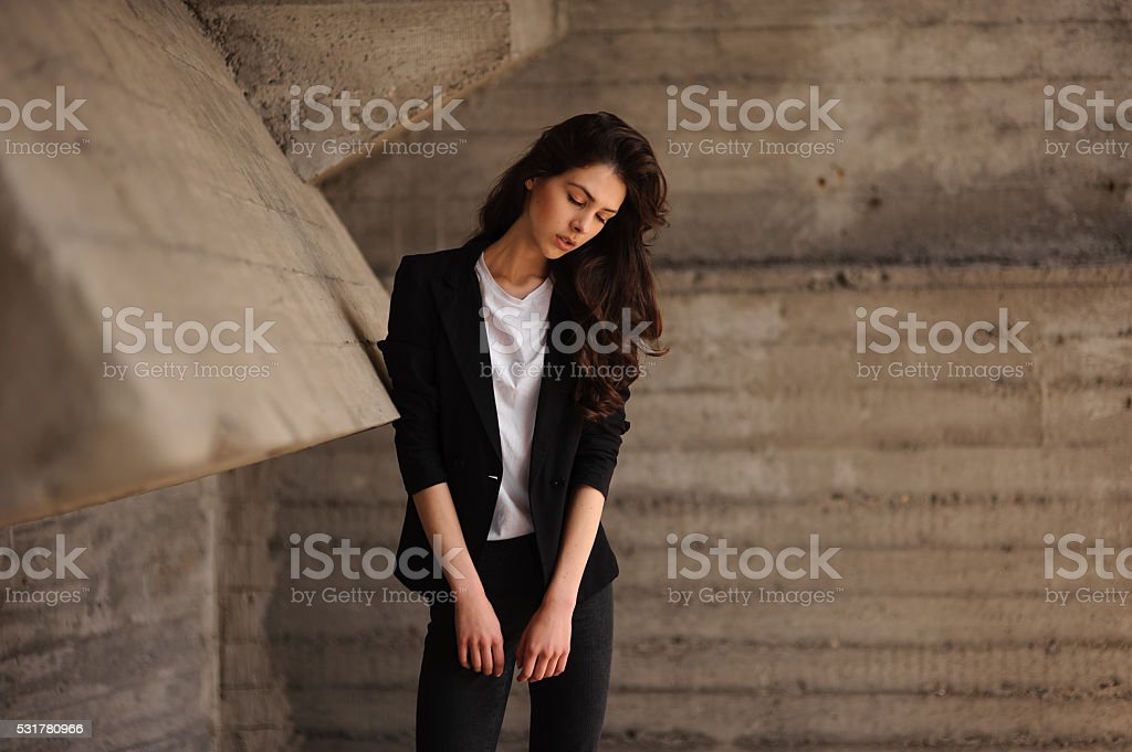 Young brunet woman standing outside in black jacket, jeans horizontal stock photo
