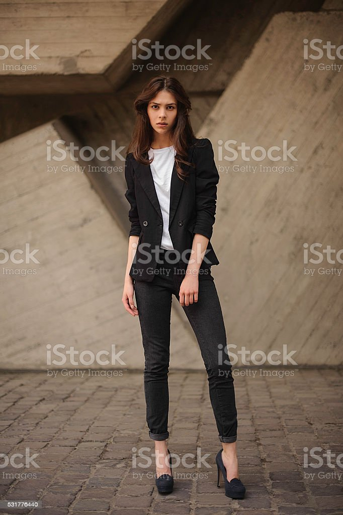 Young brunet woman standing outside in black jacket, jeans stock photo