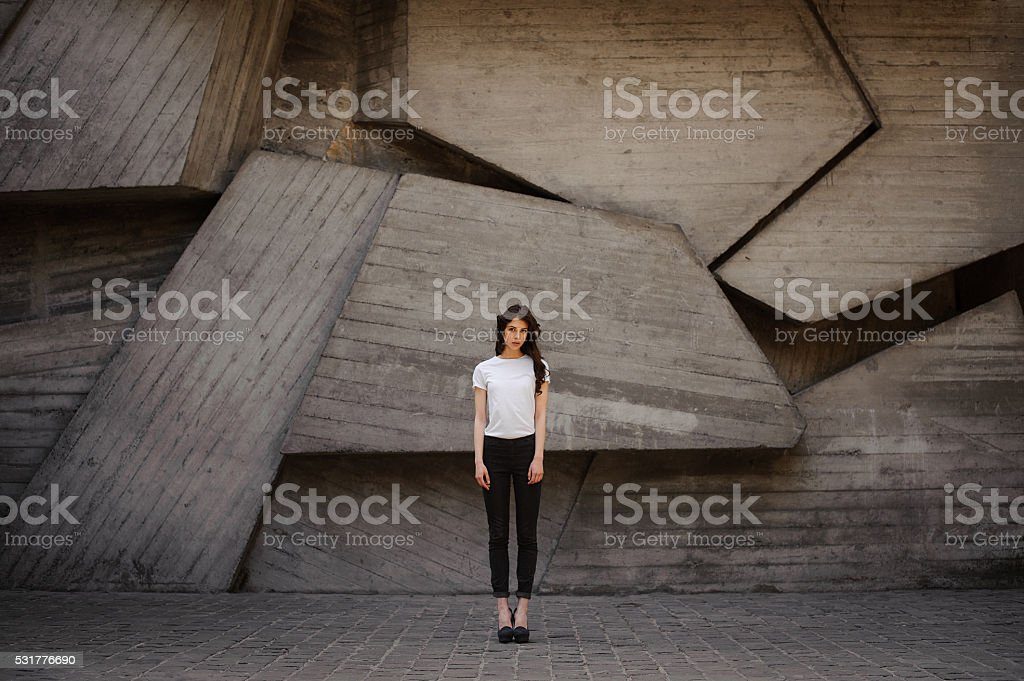 Young brunet woman standing outside in white top, jeans stock photo
