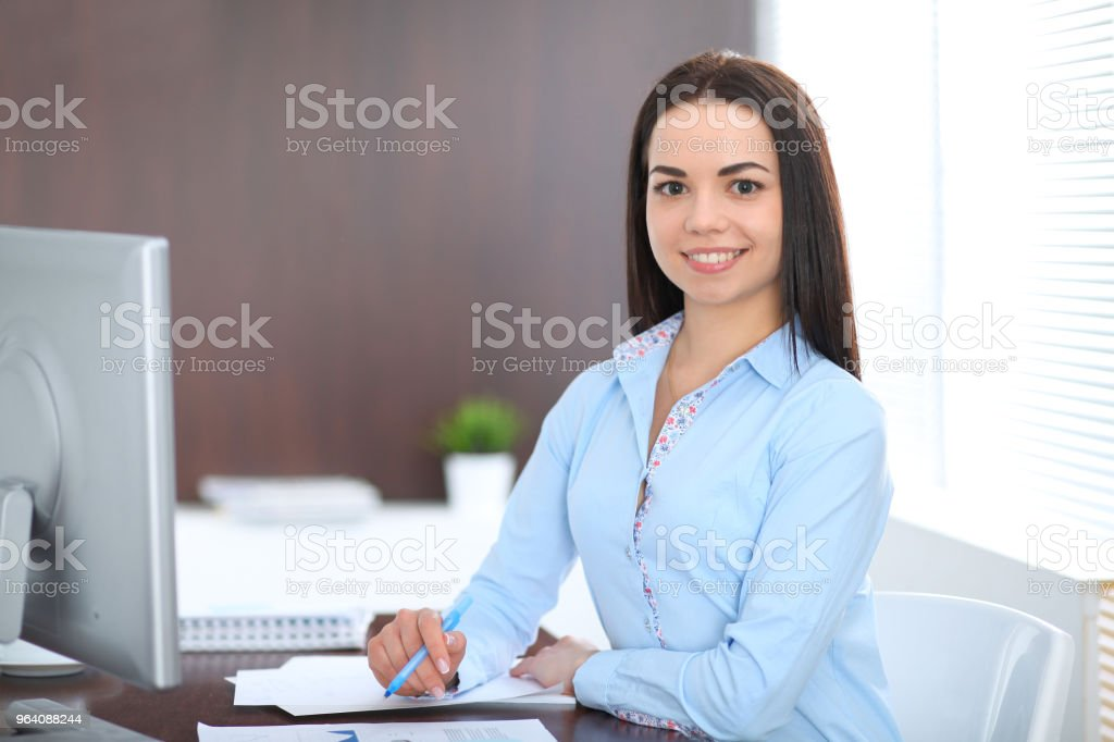 Young brunette business woman looks like a student girl working in office. Hispanic or latin american girl sitting at the desk with laptop computer - Royalty-free Adult Stock Photo