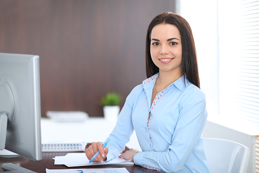 Young Brunette Business Woman Looks Like A Student Girl Working In Office Hispanic Or Latin American Girl Sitting At The Desk With Laptop Computer Stock Photo - Download Image Now
