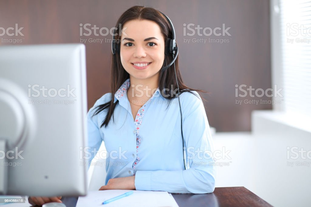 Young brunette business woman looks like a student girl working in office. Hispanic or latin american girl talking by headphones near pc - Royalty-free Adult Stock Photo