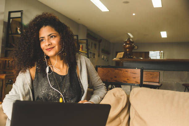 young brunette curly hair woman at a coffee shop working on a laptop - remote work imagens e fotografias de stock