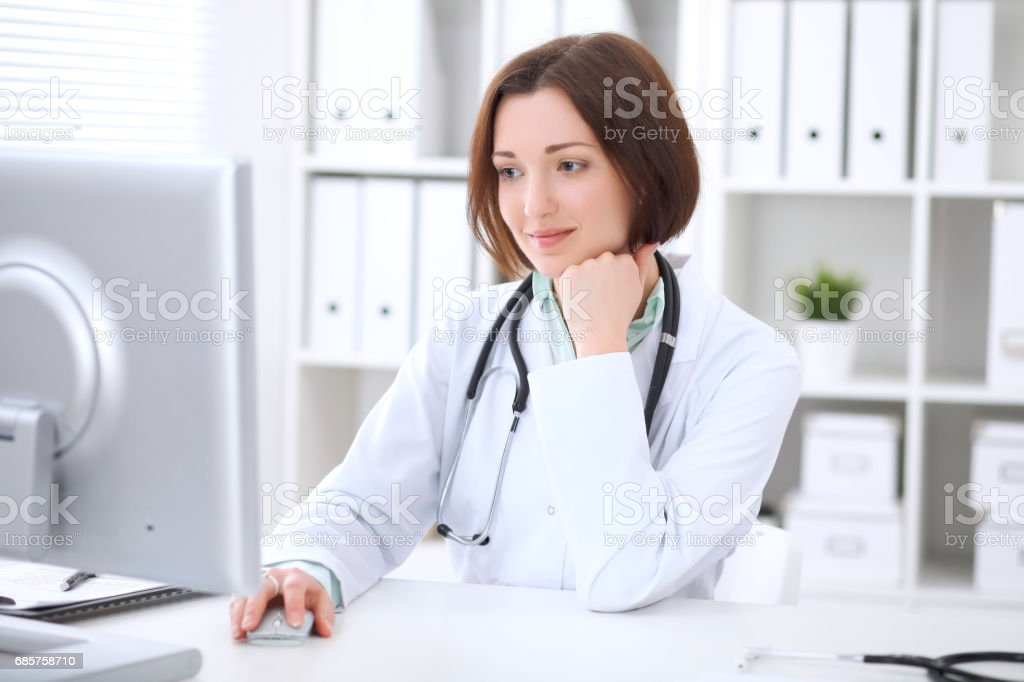 Young brunette female doctor sitting at a desk and working on the computer at the hospital office. zbiór zdjęć royalty-free