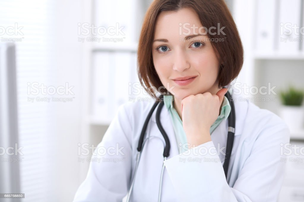 Young brunette female doctor sitting at a desk and working on the computer at the hospital office. stock photo