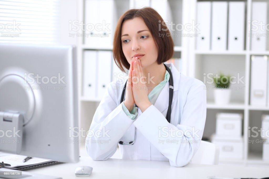 Young brunette female doctor sitting at the table and working at hospital office. foto stock royalty-free