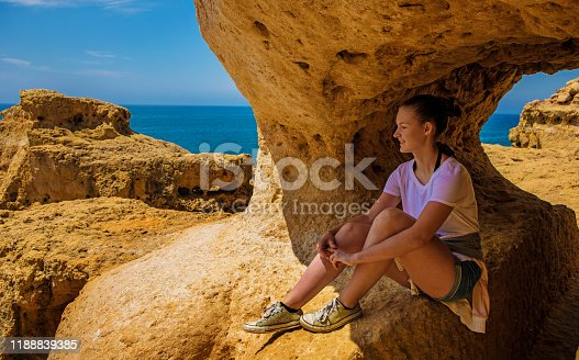Young brunette female enjoying her freedom on a beach in Alvor Portugal in late summer sun