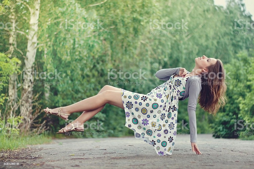 Young brunette girl in colorful dress levitating in the park stock photo