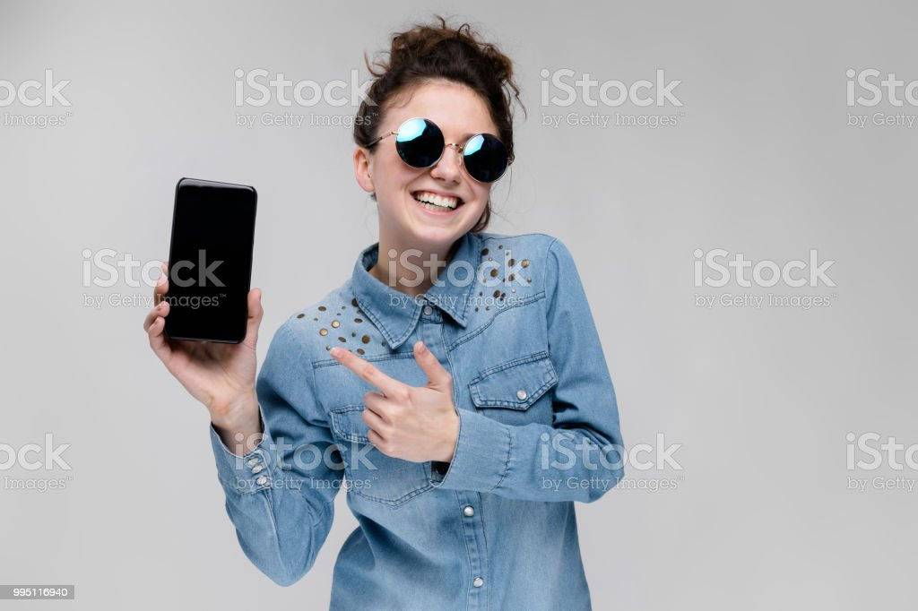 0a05feaed0 Young brunette girl in round glasses. Hairs are gathered in a bun. Girl  with a black phone. - Stock image .