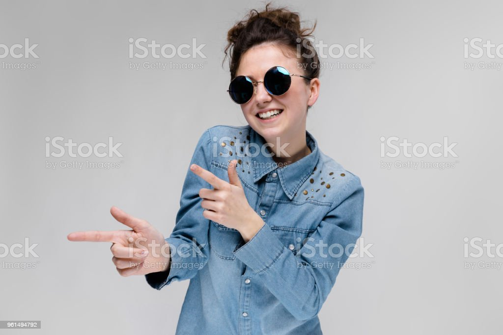 124e89678f Young brunette girl in round glasses. Hairs are gathered in a bun. The girl  points with her fingers. - Stock image .