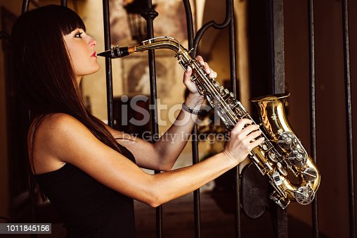 Young brunette girl having fun playing sax outdoor in a urban scene