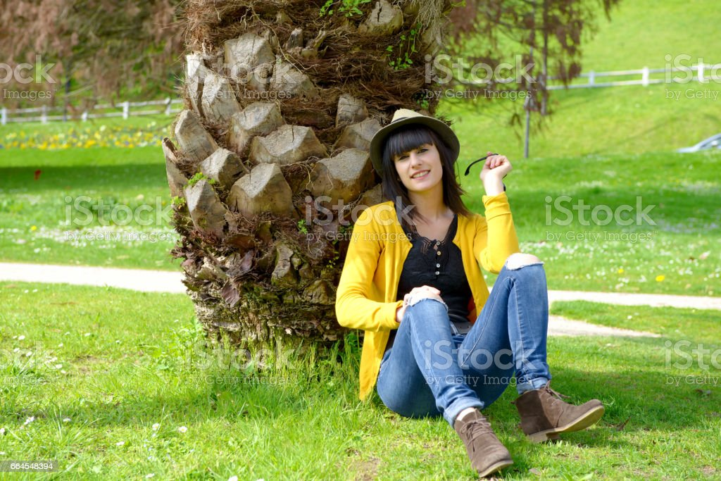 young brunette girl sitting on grass in park outdoors royalty-free stock photo