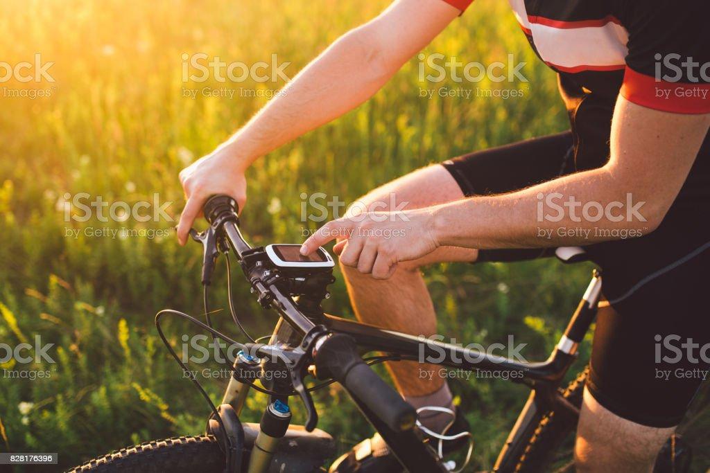 Ein junge Brünette Kerl auf einem Mountainbike verwendet einem Fahrradcomputer, ein Navigator im Feld Sonnenuntergang des Tages Lizenzfreies stock-foto