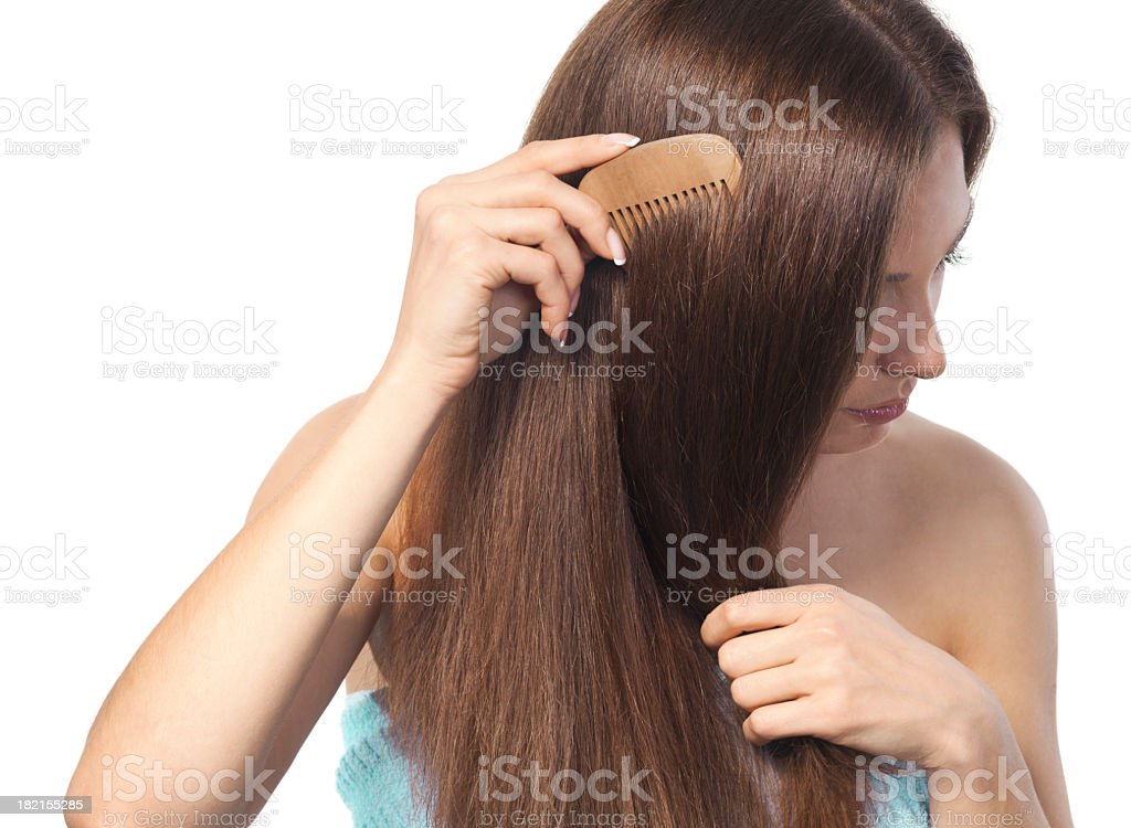 Young brunette lady combing her long hair with a wooden comb stock photo