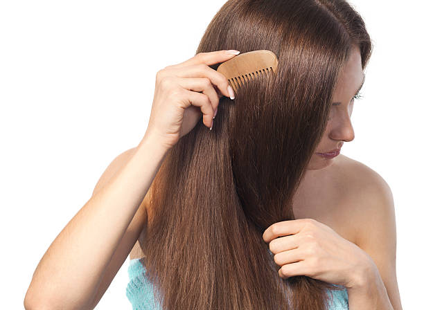 young brunette lady combing her long hair with a wooden comb - thick stock pictures, royalty-free photos & images