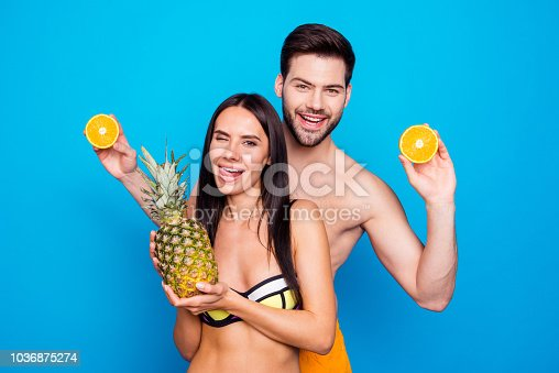 700603062istockphoto Young brunette lady laugh and hold pineapple, winks and make funny face near the man with beard wearing in swim suit isolated on blue background 1036875274