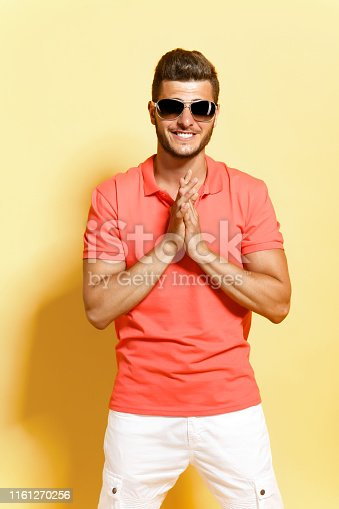 Young brunette man in sunglasses with stubble posing looking at camera folded his arms in front of him and smiles while standing against yellow background.