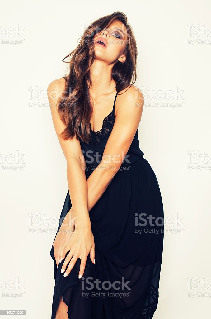 young brunette pretty woman in black dress posing on white stock photo