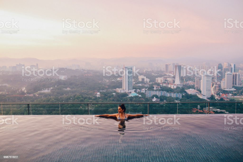 Young brunette relaxing in the pool as the sun sets above Kuala Lumpur, Malaysia stock photo