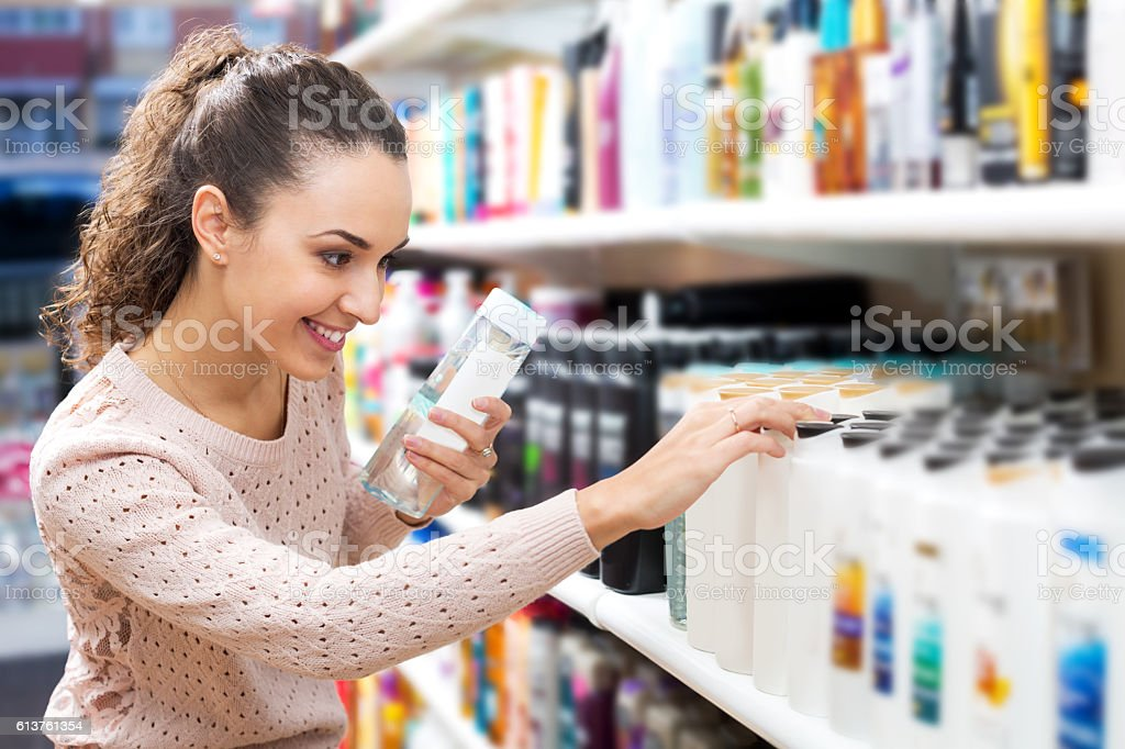 Young brunette selecting bottle of shampoo stock photo