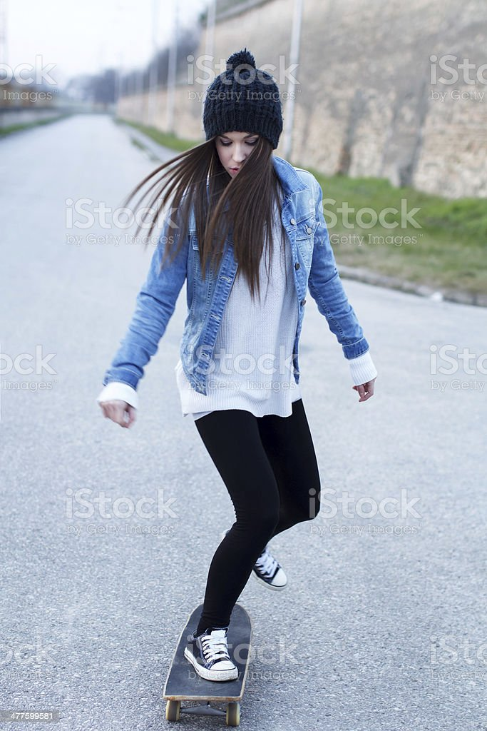 Young brunette skateboarder girl practice royalty-free stock photo