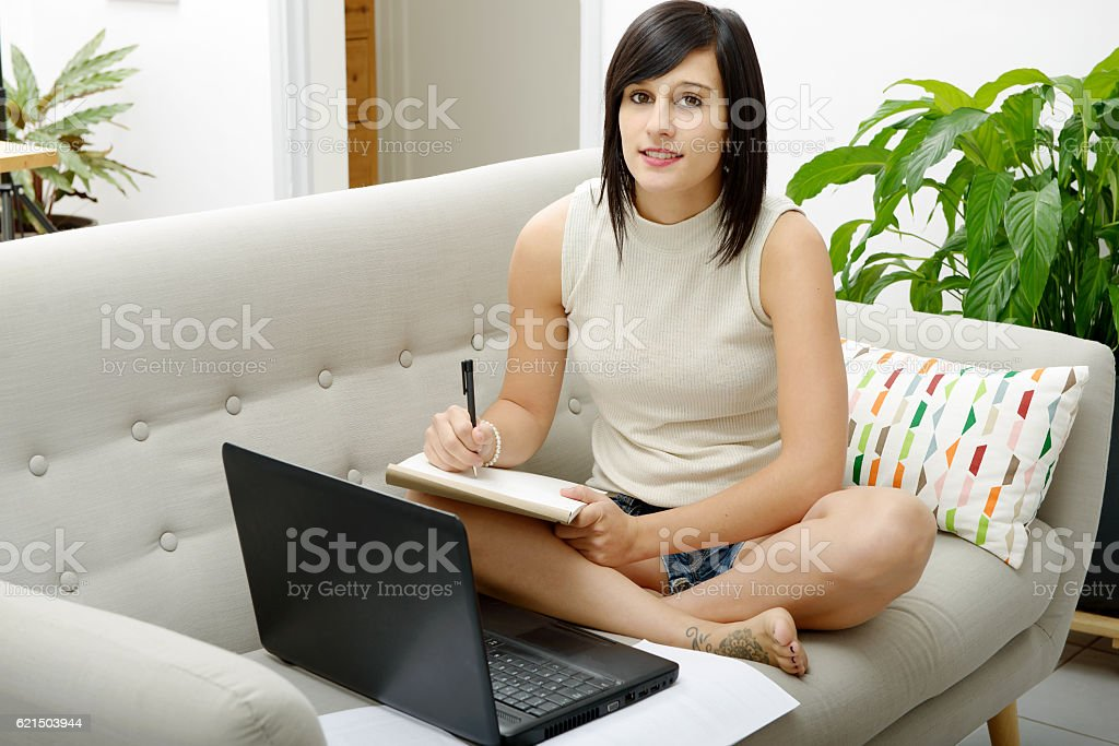 young brunette student sitting on the couch with a laptop photo libre de droits
