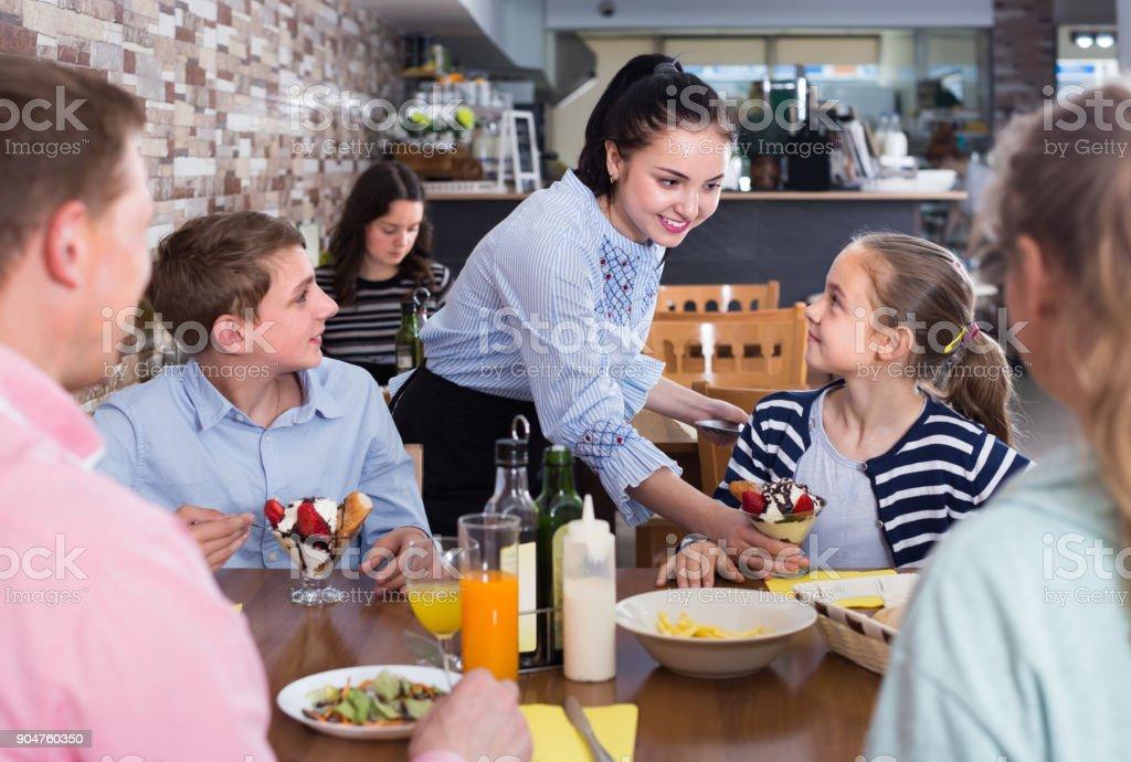 Garçonete morena jovem, servindo a família alegre no café familiar - foto de acervo