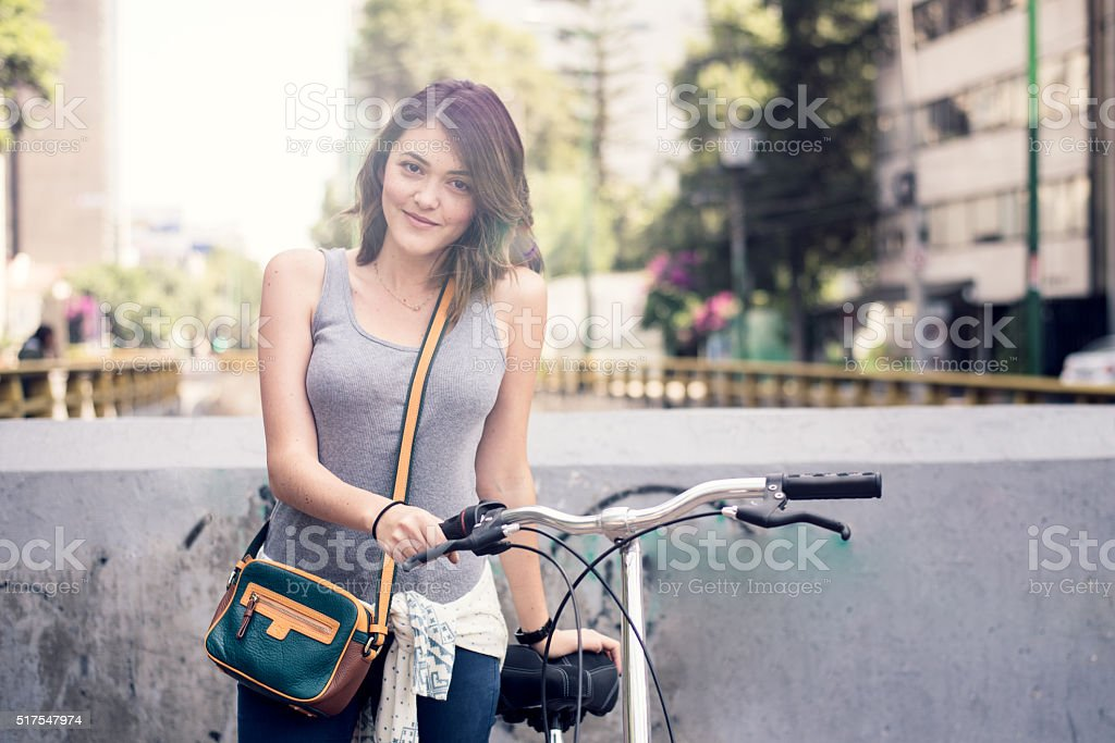 Young brunette with bicycle stock photo