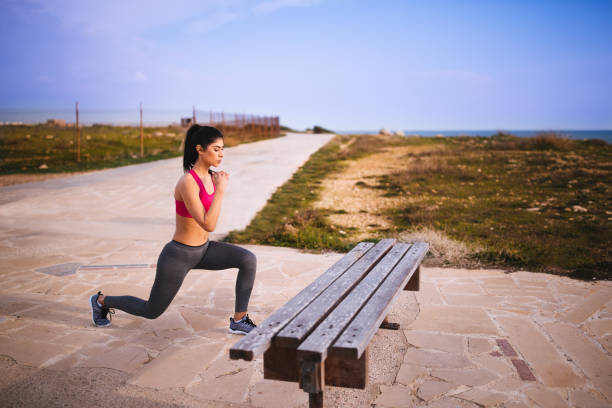 young brunette woman athlete doing lunges outdoors - lunge stock photos and pictures