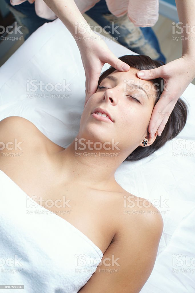 Young brunette woman getting a massage at a spa facility. royalty-free stock photo