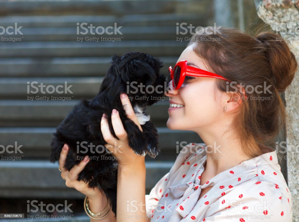 Young brunette woman hugging her lap dog puppy stock photo