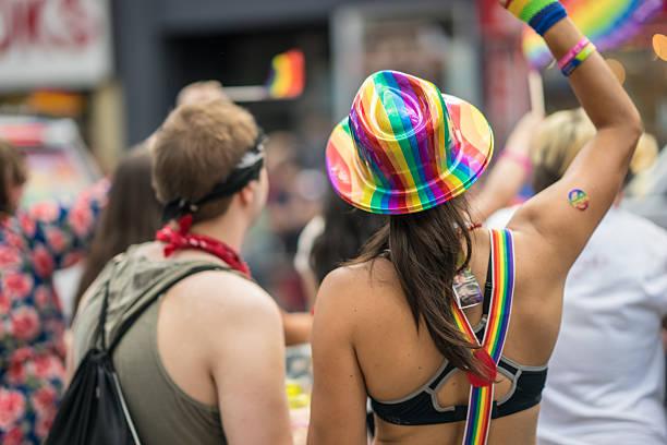 young brunette woman in a crowd celebrating pride parade. - modefarben sommer 2016 stock-fotos und bilder