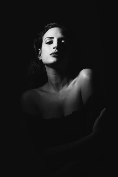 Young brunette woman in black lingerie in chiaroscuro lighting stock photo